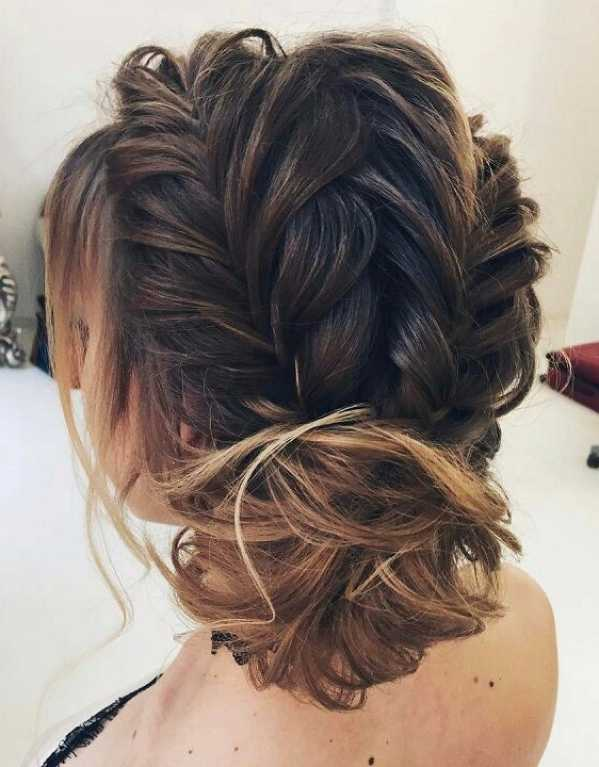 Three chunky braids piled into a bun with soft tendrils grazing your face, this one is so dreamy!