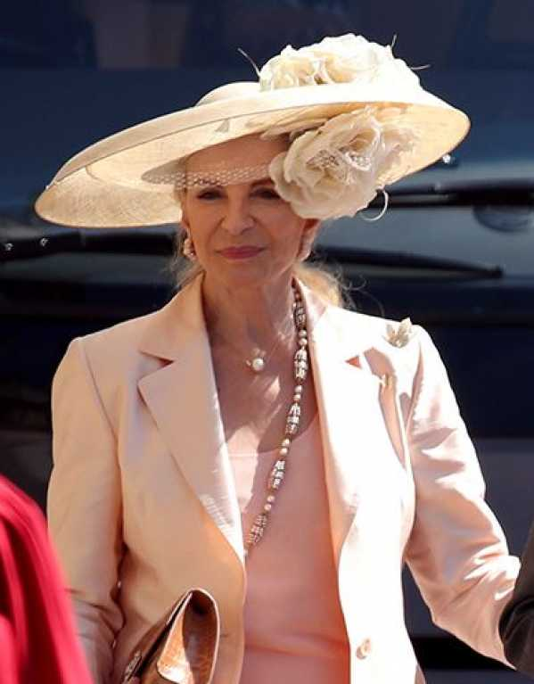 An elaborate blush pink hat with rose details on Princess Michael of Kent